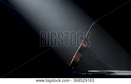 An Acoustic Guitar Resting On A Stand On A Music Concert Stage Lit By A Single Dramatic Spotlight On