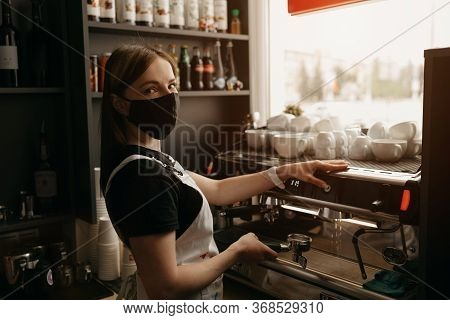 A Female Barista In A Medical Black Face Mask Rubs The Bar Counter In A Coffee Shop. A Pretty Waitre