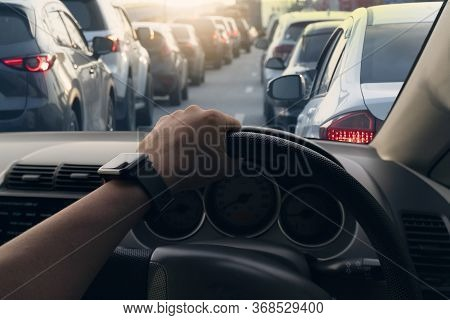 Selective Focus Hand Of People. Driving Inside Car And Many Cars On The Road Jam In Traffic Junction