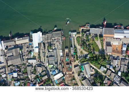 Aerial photo of town, port and fishing boats on sea in Thailand