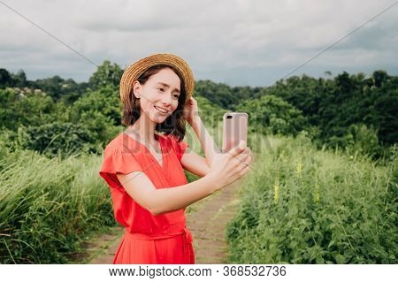 Caucasian Woman In Straw Hat And Red Dress Enjoying Vacations Travel Shooting Selfie Photo Or Video