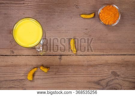 Golden Milk In A Glass Gray Cup On A Wooden Background