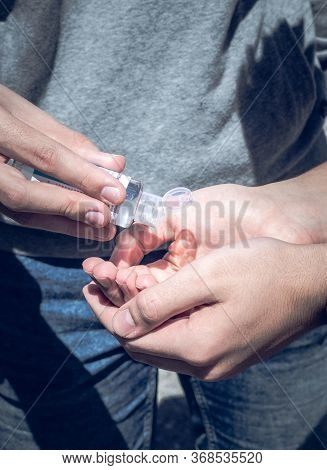 By Putting On Their Hands The Hydroalcoholic Gel To Disinfect Themselves And Protect Themselves From