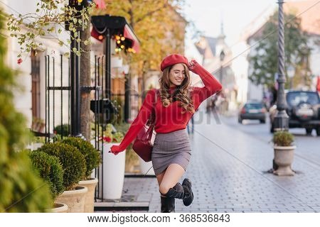Joyful Young Woman In Red Beret Dancing On Pavement With Charming Smile. Outdoor Portrait Of Gracefu