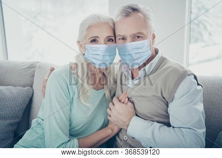 Photo Of Pretty Elderly Aged Couple Bonding Leaning Heads Holding Hands Sitting On Cozy Sofa Wearing