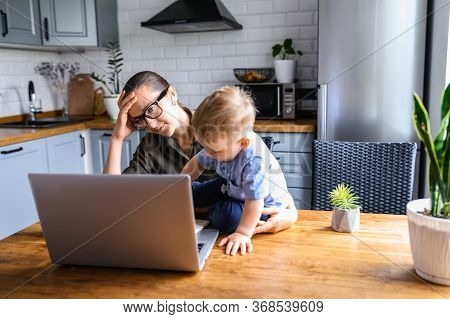 Tired Mother Works From Home While Babysitting With Toddler Boy. Mom In Glasses Sits At The Kitchen