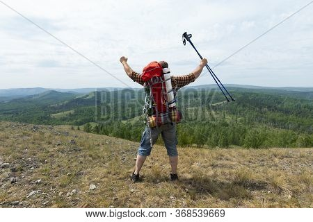 Middle Aged Hiker Backpacker Man Growing Hands With Trekking Poles During High Altitude Acclimatizat