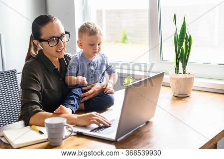 Modern Mother Works Remotely With A Kid Near. Mom And Toddler Son Sit At The Table And Are Looking A