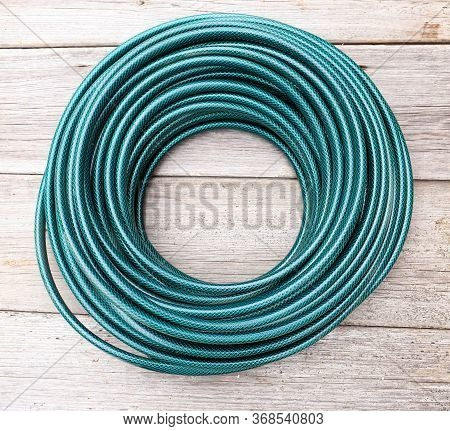 Water Hose For Irrigation Is Rolled Into A Ring. New Long Hose On An Old Wooden Background