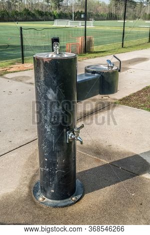 A Rusty Scratch Up Black Drinking Water Fountain With Three Spigots In A Park With Soccer Fields In