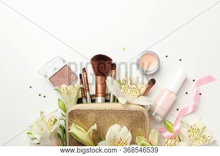 Different Makeup Cosmetics And Flowers On White Background. Female Accessories