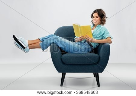 comfort, people and furniture concept - portrait of happy smiling young woman in turquoise shirt and jeans sitting in modern armchair and reading book over grey background