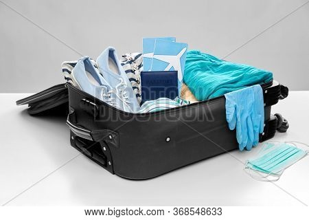 tourism, luggage and pandemic concept - travel bag packed with clothes, air tickets, passport and medical gloves with face protective masks