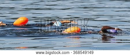 Two Black Triathletes Are Swimming Together With Orange Safety Bouys Trailinng Behind Them Training
