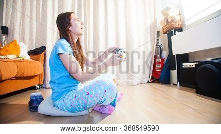 Cheerful Young Female In Casual Wear Sitting On Floor And Playing Video-games. Overjoyed Delighted W