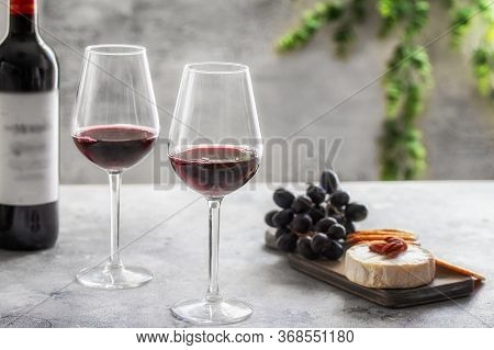 Red Wine  Bottle With  Two Glasses And Cutting Board With Different Snacks On Grey Concrete Backgrou