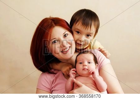 Happy Young Mother With Two Children, Boy And Girl. Portrait Of Happy Mixed Race Family: Smiling Mom