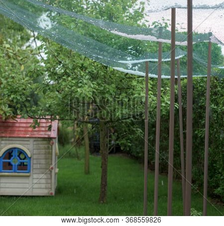 Storm Of Hail In A Yard And Protection Net