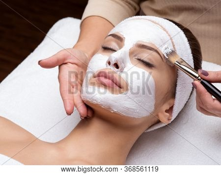 Beautiful young woman receiving facial mask at beauty salon