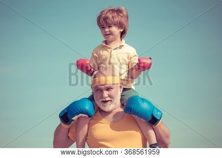 Healthy Fighter Grandfather And Grandson With Boxing Gloves. Grandfather And Grandson Doing Boxing T