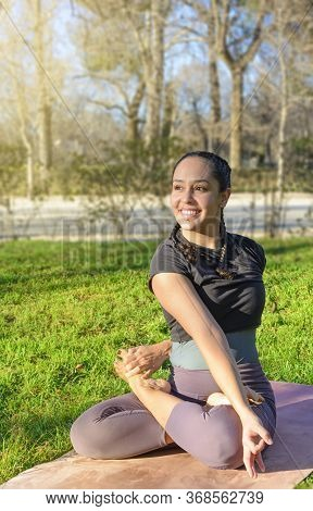 A Young Woman Practicing Yoga In A Park In The Evening. Summer