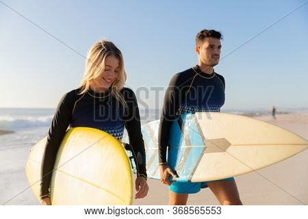 Caucasian couple enjoying time at the beach on a sunny day, holding surfboards and walking with sea in the background