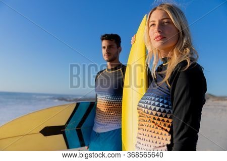 Caucasian couple enjoying time at the beach on a sunny day, holding surfboards and standing with sea in the background
