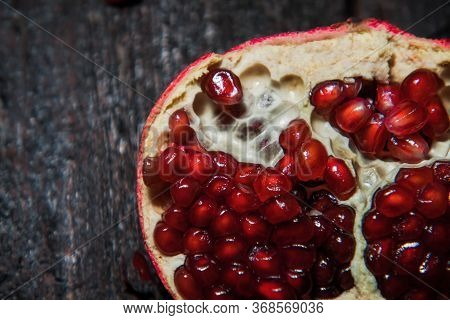 Broken Pomegranate Fruit On A Dark Background. Close-up. View From Above
