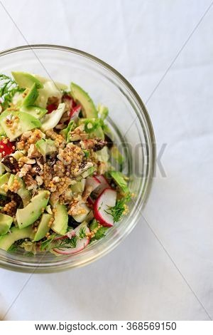 Salad In A Transparent Bowl Of Avocado, Walnuts, Green Salad, Radish French Mustard On A Table With