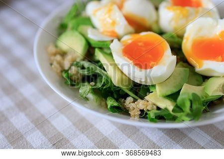 Salad With Avocado, Quinoa, Arugula, Soft-boiled Eggs On A White Plate. Close-up, Top View. Healthy,