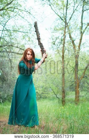 Young Woman In Spring Forest. Lady In Elegant Dress With Cudgel In Hands. Danger And Self-defence Co