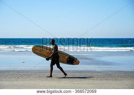Surfer In Holding A Surfboard On The Beach. Surfer Going To The Water, Del Mar Beach, California, Sa