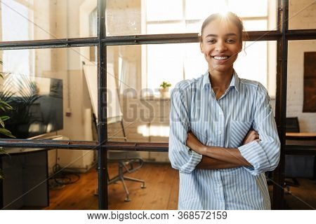 Photo of joyful african american woman with hands crossed smiling while leaning on glass wall in modern office