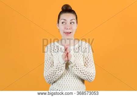 A Young Girl Looks Slyly, Rubbing Her Hands And Sticking Out Her Tongue. Isolated On A Yellow Backgr