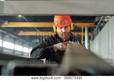 Serious bearded manual worker in ear protectors and hardhat sorting metal planks on shelf in warehouse