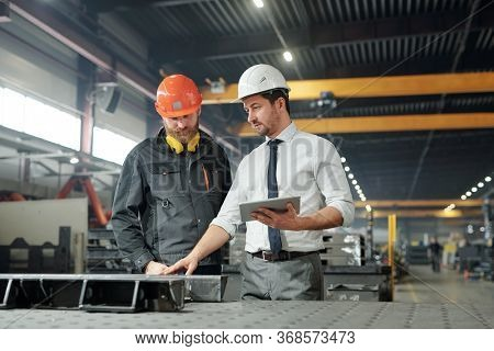 Industrial manager with tablet talking to worker and examining produced metal parts in factory shop