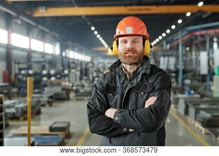 Portrait of content bearded factory worker in ear protectors and hardhat standing with crossed arms in contemporary shop of industrial plant