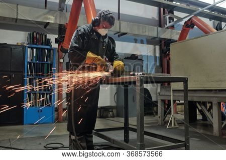 Manual worker in mask and ear protectors standing at high metal table and cutting metal with rotary tool in industrial shop