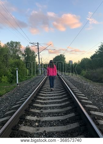 Woman Walking Away In Sunset On Train Railroad. Back View.