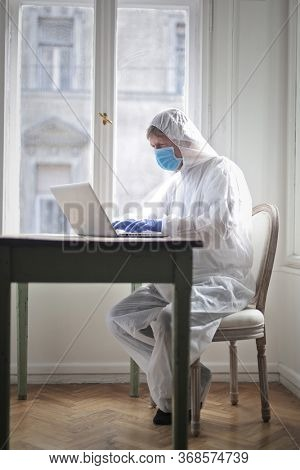 man works on computer protected by medical suit and mask