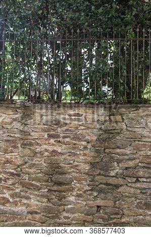 Wrought-iron Railing With Hedge And A Dry Wall. Hires Photo.