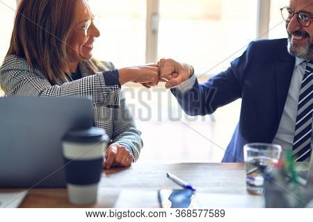 Two middle age business workers smiling happy and confident. Working together with smile on face giving fist bump at the office