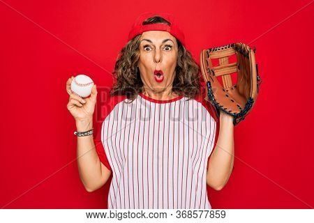 Middle age senior woman wearing baseball equiment, ball and glove over red isolated background scared in shock with a surprise face, afraid and excited with fear expression