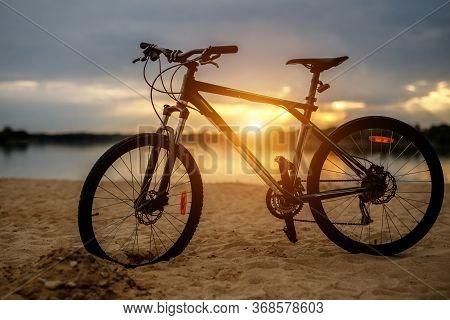 Silhouette Of Sports Bicycle On A Beach. Sunset.