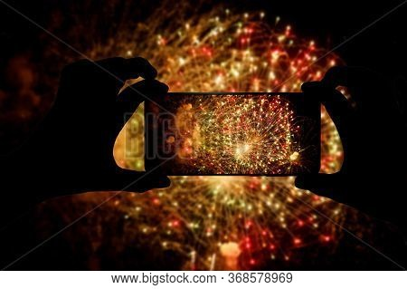 Taking The Photo Of Fireworks Via Smartphone. Broadcast Salute Video To The Internet.