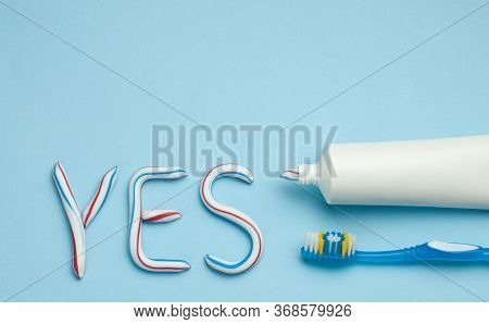 Word Yes From Toothpaste. Tube Of Colored Toothpaste And Toothbrush On Blue Background. The Concept