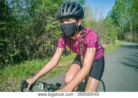 Sport cyclist woman biking on road bike wearing face mask for Covid-19 prevention during summer outdoor recreational activity. Fitness outside.