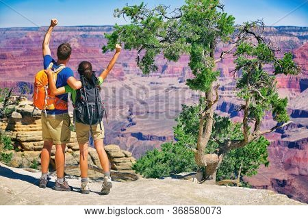 Grand Canyon hikers tourists couple cheering success with arms up happy for hike achievement. Backpackers hiking with backpacks standing at view of famous american landmark, USA trip travel.