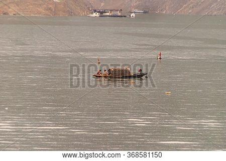 Wushan, Chongqing, China - May 7, 2010: Wu Gorge In Yangtze River. 2 Men On Small Brown Cabin Sloop