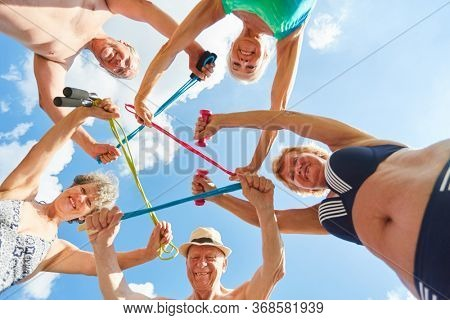 Group of vital seniors doing gymnastics exercise with skipping rope in rehab course